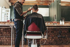 Hairdresser giving haircut to client