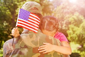 Army man hugging daughter with American flag
