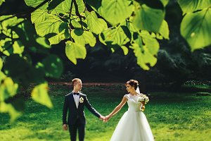 Bride and groom walking in the park