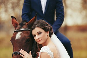 Bride stands behind a horse