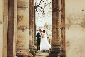 Newlyweds kiss between old pillars