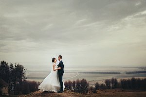 Bride and groom stand on the hill