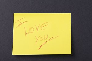 Yellow post-it on black background with a love message written on it