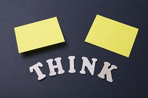 Word think next to two yellow post-its on black background
