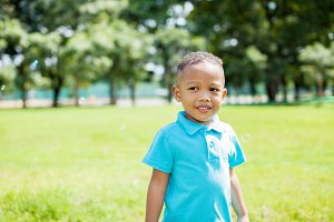 African American boy smiling in the park during summer
