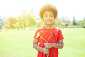Happy Smiling African American girl holding flowers in park