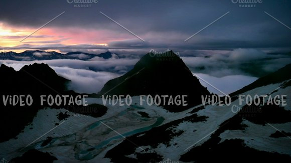 Sunset of High Snowy Tops of Mountains with Clouds Timelapse in early spring. Kavkaz region