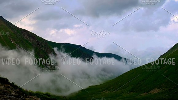 Time lapse of fog and clouds rolling over spring mountain green valley in Kavkaz region