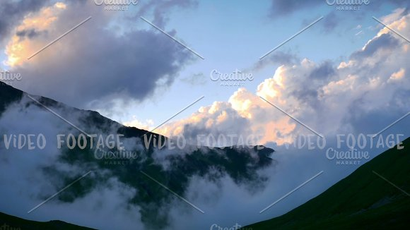 Time lapse of fog and clouds rolling over spring mountain green valley