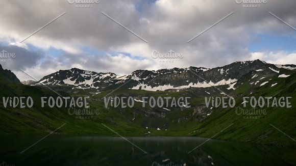 timelapse of High Snowy spring mountains with sunset clouds and peaceful mirror lake
