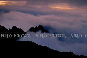 timelapse of sunset above the clouds with silhouettes of mountain tops