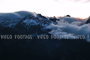timelapse of winter sunset in high snowy mountains with clouds