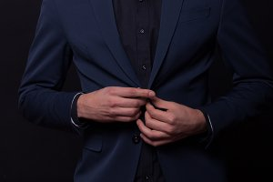 man looking down buttoning jacket