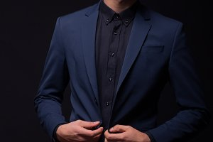 man buttoning jacket dark suit