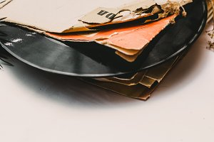 Stack of scratched dusty old vinyl records tied with rope on white background