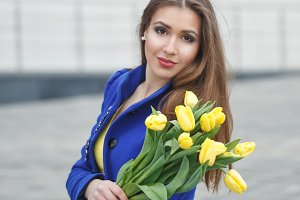 Girl with bouquet of yellow tulips