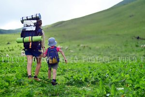 mother and her son with Hiking backpacks walking in green summer mountains