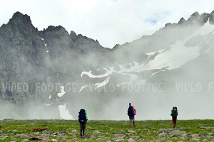 Group of tourists with Hiking backpacks coming in High Spring Mountains with Clouds