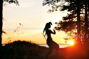 silhouette of young woman dancing in sunset