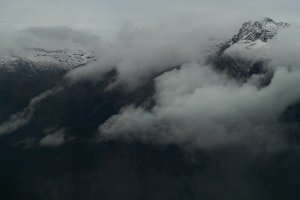 timelapse of grey high blowing snow mountains with storm clouds and strong wind
