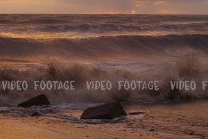 storm in the sea, big waves crashes on the beach in sunset