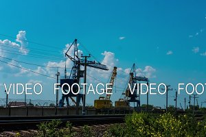 timelapse and the sunset silhouette of crane working on a construction site loading cargo train railway industry tower crane cargo crane