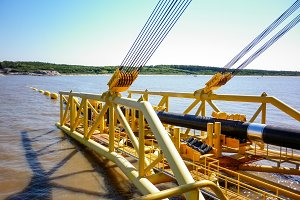 Laying of pipes with pipe-laying barge crane near the shore