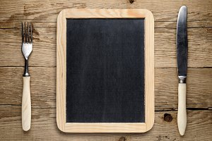 Blank blackboard, fork and knife