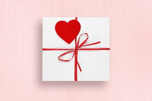 Gift box with red heart on pink