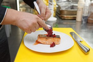 Chef is decorating salmon steak