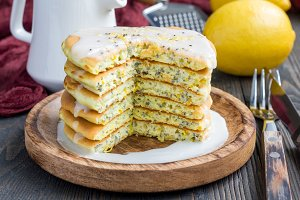 Homemade lemon and chia seed pancakes with citrus glaze, horizontal