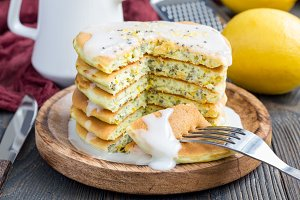 Homemade lemon and chia seed pancakes with citrus glaze, horizontal