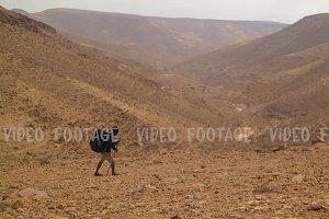 Black Traveler with Hiking Backpack in the Desert