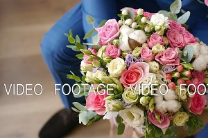 Groom is holding bridal bouquet in the hands of