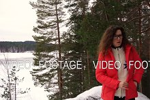 curly woman makes selfie with snowy landscape