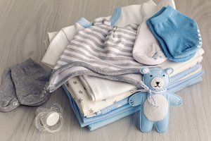 baby clothes with diapers are stacked
