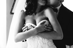 Groom holds bride's chest