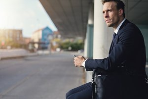 Pensive businessman holding phone and looking away