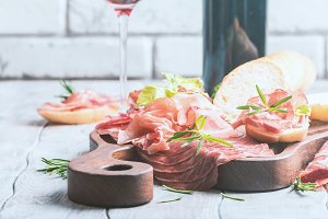 Concept of italian food with red wine, melon and prosciutto