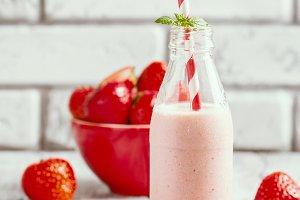 Strawberry smoothie or milkshake in a glass bottle