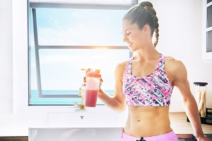 Smiling sportive person holding shaker with drink