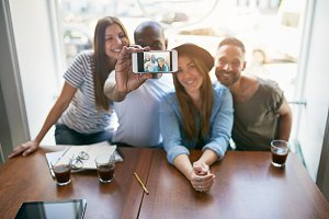 People taking selfie while sitting at table