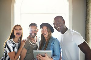 Laughing people standing and holding touch pad