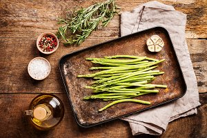 raw asparagus with salt and olive oil on pan,