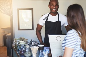 Black smiling cafe worker talking to customer