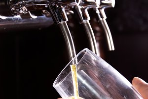 Bartender and beer from dispenser.