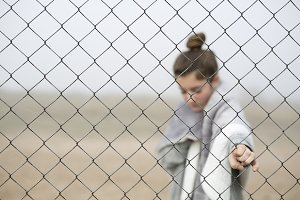 Girl behind a fence