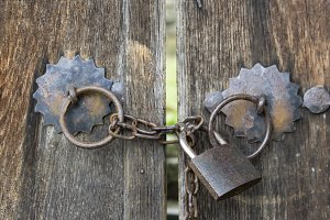 Old wooden gates locked on iron padlock with chain