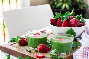 Green spinach smoothie with strawberry