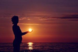 Silhouette holding sun